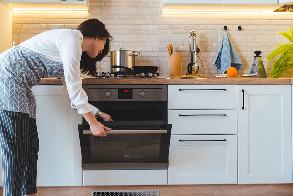 young woman open oven to cook with propane